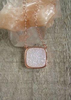 A gorgeous natural white druzy shimmers and shines along a delicate 14K rose gold fill cable chain. I am so excited about this new pendant. Its the largest of the titanium druzies that I carry, and its a real stunner. Natural white druzy stone has a light AB (rainbow-like) coating, which gives it a slight iridescence. This druzy is not coated with titanium like most of the other druzies that I carry, so its sparkle is much more subtle. Druzy is housed in a bright rose gold plated frame…