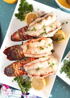 Overhead shot of three baked Lobster Tails with lemons and parsley on a white platter. The best way to cook a frozen lobster tail at home.Baked Lobster Tail is simple and fool proof. Tender, juicy and sweet.this is the perfect dinner to impress. Baked Lobster Tails, Broiled Lobster Tails Recipe, Broil Lobster Tail, Grilled Lobster, Broiled Seafood Platter Recipe, Lobster Dinner, Fresh Lobster, How To Cook Lobster, Lobster Feast