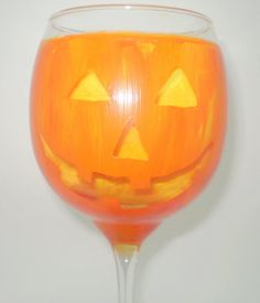 A classic Jack O Lantern face painted on a wine glass painted like a pumpkin. The 'cutouts' are clear so whatever color beverage is added will show through the eyes, nose, and mouth (Picture number 4 is the glass without yellow paper inside). Great with OJ for a classic look or red wine for a eviler look. A wonderful addition to any Halloween party or as a party favor for special guests or just the Halloween fanatic in your neighborhood.