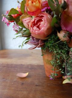 Pretty table arrangements of garden roses and fragrant herbs in terracotta pots | The Natural Wedding Company