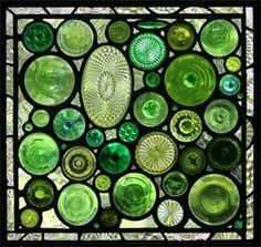 """GREEN BOTTOMS II :  26"""" x 25""""  The second Green Bottoms was made in response to the overwhelming reaction we received to the first Green Bottoms, which was featured in newspapers and magazine articles. The window is comprised of highly textured bottle, vase, serving plate and stemware bottoms along with a variety of antique pressed glass jewels and objects.   The background is a variety of clear textured glasses and the border is composed of pale lavender """"Depressions Glass"""" plates."""