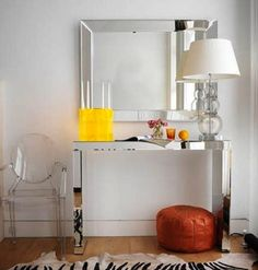 a mirrored console table pairs up with a glass lamp and lucite chair