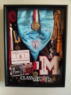 My daughter's high school graduation shadow box. 2013 Included are her National Honor Society stole, Honor cord for blood donation, tassel, International Thespian Society Medal, Summa Cum Laude Medal, graduating with Honors cord, Chorale gift, Academic letter, Top 20 Medal, announcement, invitation to her party and 6 Presidential Awards for Excellence in Education. The banner at the bottom & shadow box came from Michaels Crafts