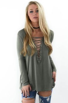 An olive top featuring a lace up front, deep v-neckline, long sleeves, and no lining Material is Rayon and Spandex Model Elizabeth is 5'6 wearing a small Bust L