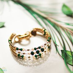 Show off your sophisticated style with this handmade bangle bracelet that is made with radiant 22K Gold Plated beads,  beautiful glass crystal beads in emerald green, amber and clear, and a large gold-plated lobster clasp that effortlessly secures the bracelet to you wrist.
