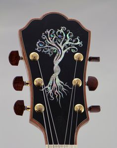 "Buscarino Tree of Life: My customer came to me with the idea to have a very unique guitar built by me and after kicking around many ideas he suggested the ""Tree Of Life"" theme. It sort of took off from there. Once we settled on the Tree headstock inlay we collaboratively decided that the fingerboard inlays should be Leaves. We had Master Inlay Artist Larry Robinson do the inlays and he suggested to do the outline of the leaves on the fingerboard in Gold Leaf to make them pop and shine."