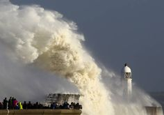 TOPSHOT - Huge waves strike the harbour wall and lighthouse at Porthcawl, south Wales, on October 16, 2017 as Storm Ophelia hits the UK and Ireland. Ireland was hit by an 'unprecedented storm' on Monday that left two people dead, 120,000 homes and businesses without power and closed every school in the country. The storm also sent strong winds over the southwest of England and the south and west of Wales. / AFP PHOTO / Geoff CADDICK