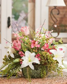 "Soft pink artificial tulips, casablanca lilies, cherry blossoms and ferns flow from a green 8"" diameter cache pot. This casual yet sophisticated ""just picked from the garden look"" will add texture, color and life to a large coffee or dining table.$119"