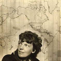 Amelia Earhart in front of a map of her proposed trip around the world