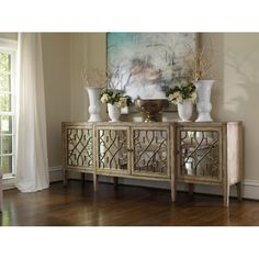 Perfect for displaying a lush floral arrangement or stowing board games and DVDs, this handsome sideboard showcases 4 mirrored doors with fretwork overlay.
