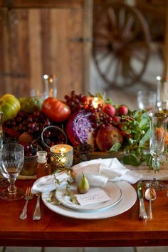 dark table, white linen runner, vegetable centerpiece (sort of a cornucopia), sliver utencils, white plates, low votives, white napkin with contrast stitching ... tomatoes, cabbage, radishes, grapes, etc...