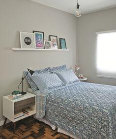 Um tom neutro de prata nas paredes destaca os quadros coloridos apoiados na prateleira. Nas laterais da cama, ela seguiu a tendência de criados-mudos descombinados, com luminárias também diferentes. Acrílica, na cor Prata, ref. C161, da Suvinil.