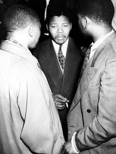 """Jurgen Schadeberg / AP Mandela, center, meets with fellow ANC Youth League leaders Walter Sisulu, left, and Harrison Motlana during the """"Defiance Campaign"""" trial at the Supreme Court in Johannesburg in 1952. The campaign encouraged people to defy the apartheid laws, a system of strict racial segregation meant to ensure the continued economic and political dominance of white South Africans. Mandela was given a suspended prison sentence."""