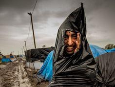 """Un migrant de la """"jungle"""" à Calais se protège à l'aide d'un sac en plastique"""