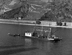 """Ein besonderes Schiff (""""Peilrahmenschiff"""") liegt, von einer Kette am Bug gehalten, im Rhein. Auf ihm sind mehrere Personen mit Peilarbeiten beschäftigt. An dem Schiff hat ein kleineres festgemacht, ebenso zwei Boote. Auf dem Rhein bei Oberwesel werden auf einem speziellen Schiff mittels eines """"Peilrahmens"""" Messungen bzw. Peilungen durchgeführt. Man kann so die Wassertiefe feststellen. Diese Arbeiten standen im Zusammenhang mit der Beseitigung von Untiefen im Strom"""