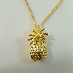 """Golden Pineapple Necklace This lovely necklace has a cute detailed pineapple pendent on it. The tropical island fruit has a pointed leaf top and the bottom has diamond shapes to give it depth. Brand new and unused. The charm is 1"""" and 1 1/2cm wide on a chain that is 26"""" long. Other great tropical fruit themed items in my closet! Jewelry Necklaces"""