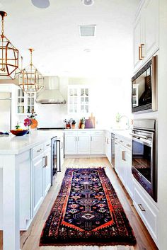 Elegant kitchen with boho details - love the rug and the light fixtures