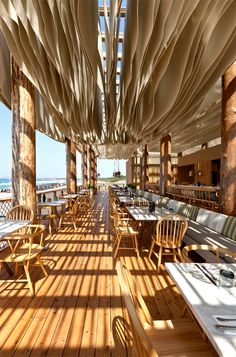 Bar bouni is a restaurant on the beach, Part of the Costa Navarino.   The restaurant sits on a wooden platform elevated from the sand allowing the waves to break underneath it. The structure of the building is formed by a grid of natural wooden columns;  Over the table area an inverted field of hanging fabric sheets forms the canopy that sways soothingly in the dissipated wind, allowing air to circulate and the space to stay cool.