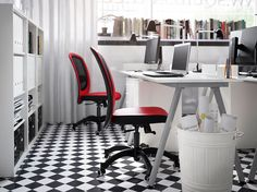 A small office with white desks, drawer units, shelf units and swivel chairs in red