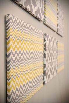 This would be so easy to make :) Blank canvases with cute fabric stapled over them. Perfect for a yellow and gray bathroom.