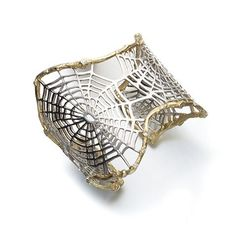 "This sterling and 18k gold cuff bracelet is part of the ""Spider Web"" series by K. Brunini Jewels. Look closely and you'll see that rose-cut diamonds are placed along the gold border."