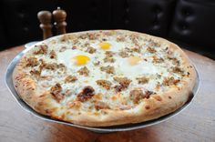 "SANTINO COLAZIONE 14"":  This savory, red-sauce based pizza has a unique array of toppings. Check it out—Pancetta, Parmesan, chives, house-made Italian sausage, Canadian bacon, red onions, and mozzarella, all topped with three cracked eggs. Looking for ""breakfast pizza?"" this might be your pie."