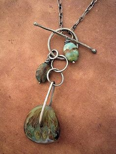 Ebb and Flow Necklace by Rebecca Bogan      Closing in the front with a handmade toggle clasp. Featuring one of Harold Williams Cooney's glass art beads.