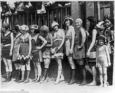 A beauty contest in 1920 shows a group of women wearing swimming costumes and long socks a...