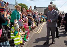 Crowning glory: School children in homemade crowns welcomed the royals