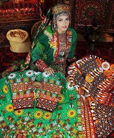 Türkmen kızı, ulusal giysileri ve ünlü Türkmen halılarıyla...