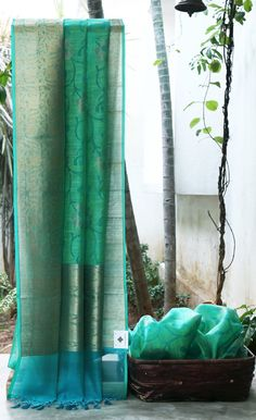 ALLURING GREEN SOUTH KORA IS INTRICATELY WOVEN WITH TURQUOISE BLUE FLORAL BODY HAS ENIGMATIC WOVEN GOLD ZARI BORDER AND PALLU WHICH GIVES THE SAREE DAZZLING LOOK.