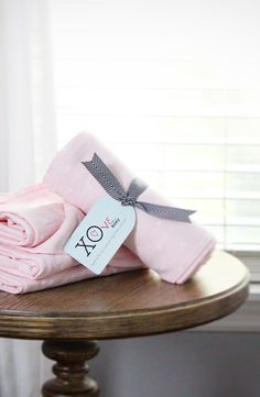Pink polka-dot bamboo muslin swaddle blanket from the XOve Baby Pearl Collection. The extra-large and baby soft swaddling blanket that gives back for every purchase.