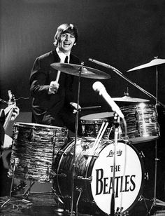Ringo Starr grins while playing the drums during the Beatles' performance on the Ed Sullivan Show in February 1964.