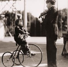 """Charlie Chaplin playing his violin for little Jackie Coogan on the set of """"The Kid""""."""