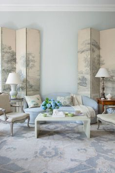 A pair of 1790s Zuber screens introduces an Old World landscape into this predominantly pale blue drawing room.  Custom sofa in DeLany & Long canvas. Cashmere-and-wool throw, Nantucket Looms. Caryatid console, John Rosselli Antiques. Image originally appeared in the March/April 2013 issue of VERANDA. INTERIOR DESIGN BY FRANK BABB RANDOLPH