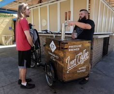 Joel Davis serves a cup of coffee to Nathan Connors, left. Davis uses a new process for brewing coffee with high-pressure nitrogen. It comes out of a tap looking like a Guinness draught beer, complete with foam. He sells his Commune + Co. coffee from a custom-built tricycle he pedals around Ybor City.
