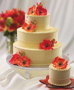 Decoración de torta de color blanco con rosas de azúcar de color rojo coral.