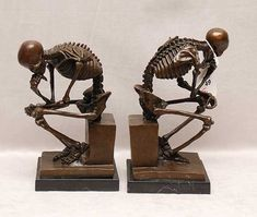 pair of bronze skeletal bookends on marble base