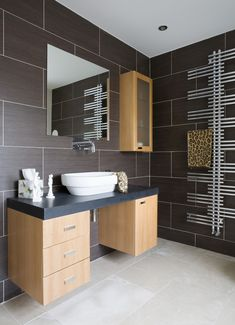 Large brown tiles are paired with modern cabinetry and a fun floor-to-ceiling towel rack.