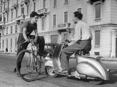Two Men Talking in Street with Vespa Scooter and Bicycle Photographic Print