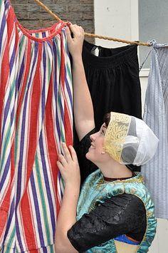 Urker vrouw in klederdracht hangt de was op zonder knijpers. Twee in elkaar gedraaide kort (niet te strak gedraaid). De waslijn hangt normaal gesproken slap. Als de was is opgehangen komt er in het midden een stok(raggebol) onder om de lijn strak te zetten.