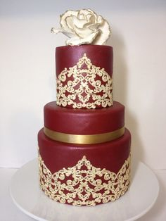 Burgundy and gold wedding cake with sugar lace and gold tipped giant rose topper