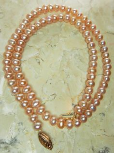 A classic pearl necklace in pale pink color with a 14K yellow gold clasp. The color on these pearls has an iridescent purple shine. Each pearl measures approximately 5.5mm in diameter. The strand is 16.5 long including clasp when unclasped and layed out flat. The pearls are not perfectly round but are nicely matched in color and size and in excellent condition. The pearls are strung on a strand, these do not have knots between each pearl. The clasp is a hook and lock style decorative…