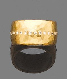 A gold and diamond ring, by Malcolm Betts  The 22 carat gold band of hammered finish, highlighted with a line of brilliant-cut diamonds, maker's mark MPB, London hallmark, ring size L, maker's box and case