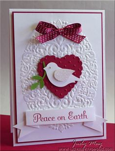 handmade Christmas card ...  white with red accents and a pop of green ... two-step punched bird disguised as a dove of peace ... luv his glittered wing and the glittered embossed oval ... Versamark lightly brayered on and the heat embossed with irredescent powder ... delightful card!! ... Stampin' Up!