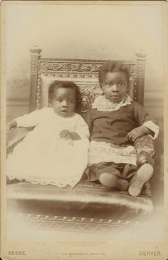 PORTRAIT OF TWO BRIGHT EYED AFRICAN AMERICAN CHILDREN IN DENVER, COLORADO.