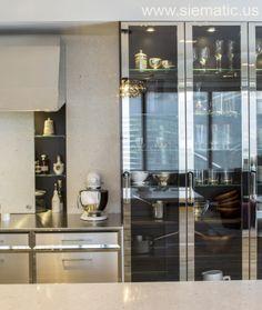 A sliding stone backsplash provides elegant hidden storage, as showcased in the redesigned SieMatic New York showroom.