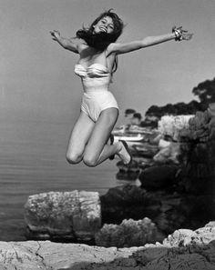 ST.-Tropez, France - Brigitte Bardot jumping in front of her villa, 1955. By Philippe Halsman. S)
