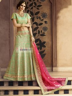 In love with pastel colors? Choose this awesome, fully embroidered, light green lehenga choli that is very unique and stylish. Paired with a reddish pink net dupatta, this amazing youthful wedding lehenga dress is a cut above the rest, thanks to its splendid and very thoughtfully placed embroidery. It's a creation that will never go out of style!