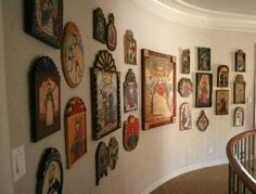 The curved wall of a staircase landing displays the couple's collection of retablos, small oil paintings on tin, zinc or wood depicting saints and often used as home altars.